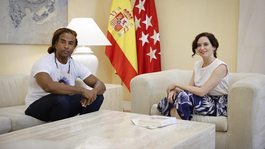 El artista Yotuel sentado a la izquierda de la presidenta en unos sofás con una mesa en medio
