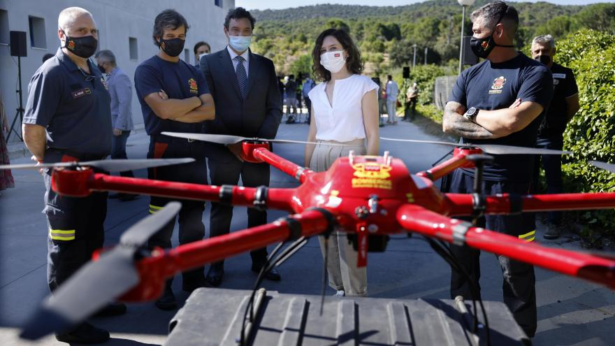La presidenta con algunos bomberos mirando un dron