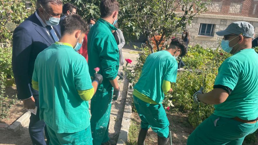 El consejero junto a un grupo de jóvenes vestidos con uniforme verde y haciendo labores de jardineria