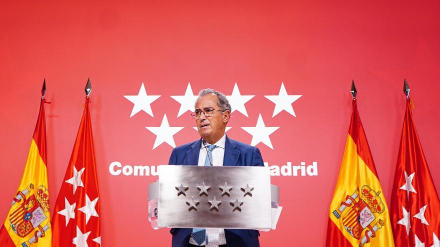 El consejero interviniendo en el atril con el logo de fondo de la Comunidad de Madrid