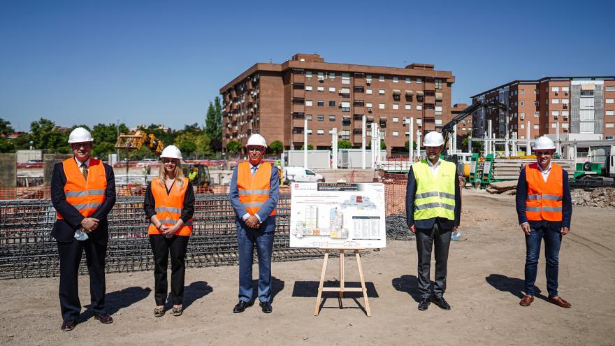 El consejero junto con el resto de miembros posan en las obras del nuevo colegio junto al plano del mismo