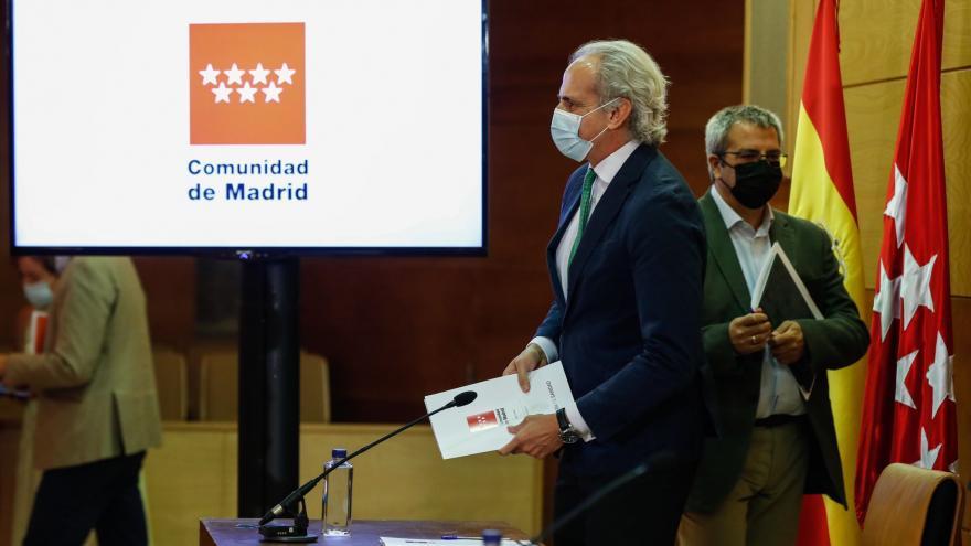 Ruíz Escudero ante la mesa de la rueda de prensa con cartel detrás de la Comunidad de Madrid