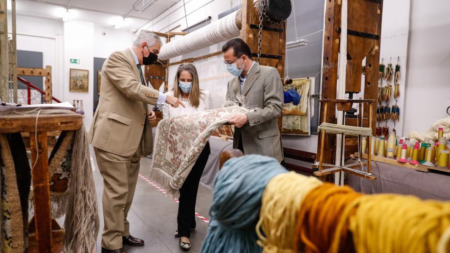El consejero junto con trabajadores de la fábrica de tapices mirando una alfombra