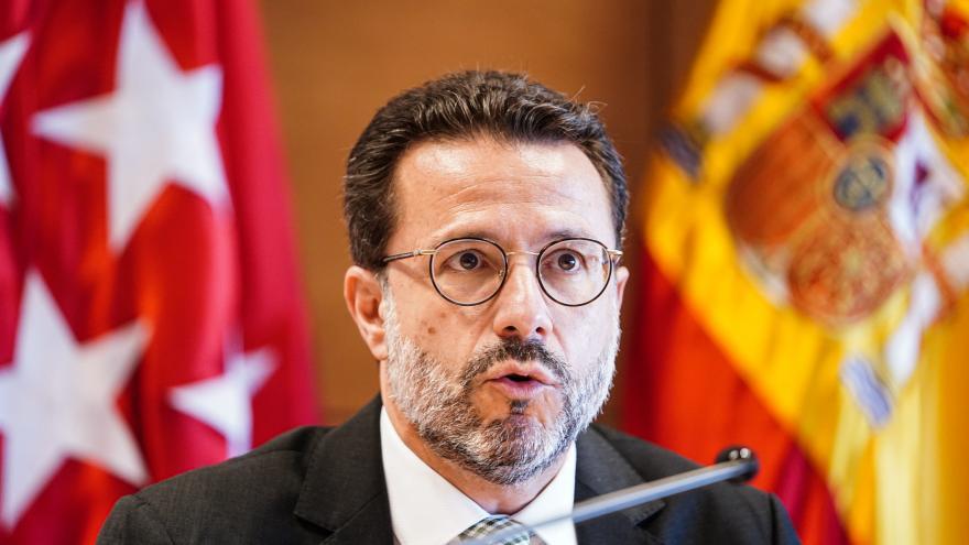 Primer plano del consejero con la bandera de España y la de la Comunidad de Madrid de fondo