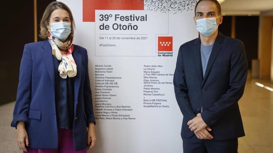 Dos personas posan con el cartel de actuaciones del festival de otoño