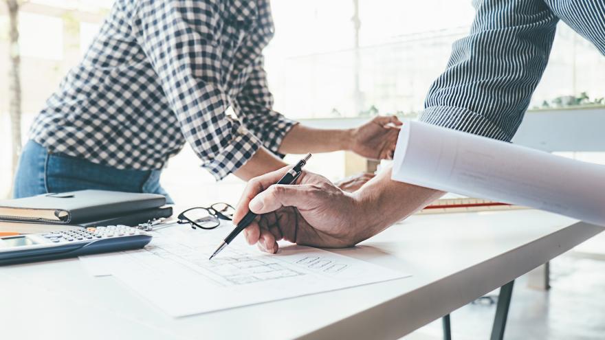 Mesa con manos trabajando en papeles