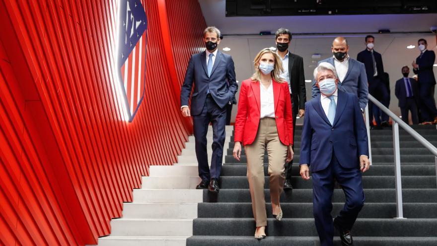 La consejera bajando las escaleras del Wanda Metropolitano junto al presidenta del club y el escudo del equipo de fondo