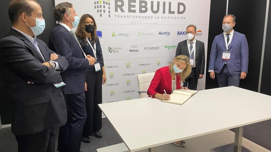 La consejera firmando el libro de visitas del evento
