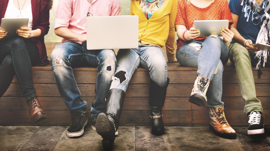 Plano de las piernas de jóvenes entados con un ordenador