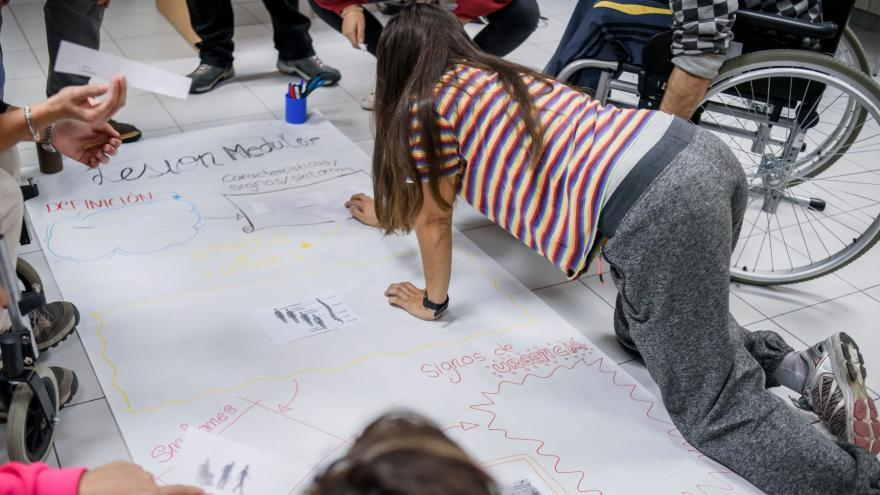 Joven escribiendo un mural en el suelo
