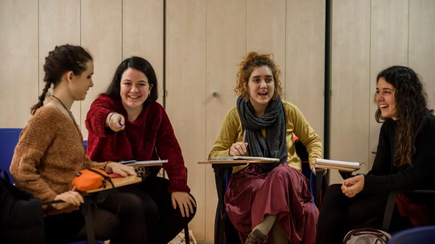 Tres jóvenes en un curso mirando a cámara