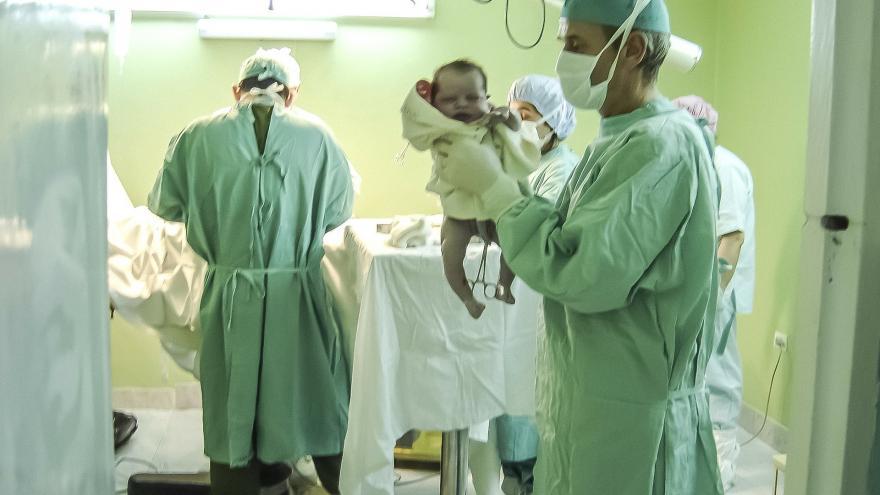 Equipo sanitario con un bebé recien nacido
