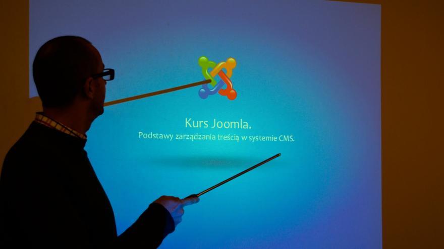 Silueta de profesor mostrando algo en una pantalla con un puntero
