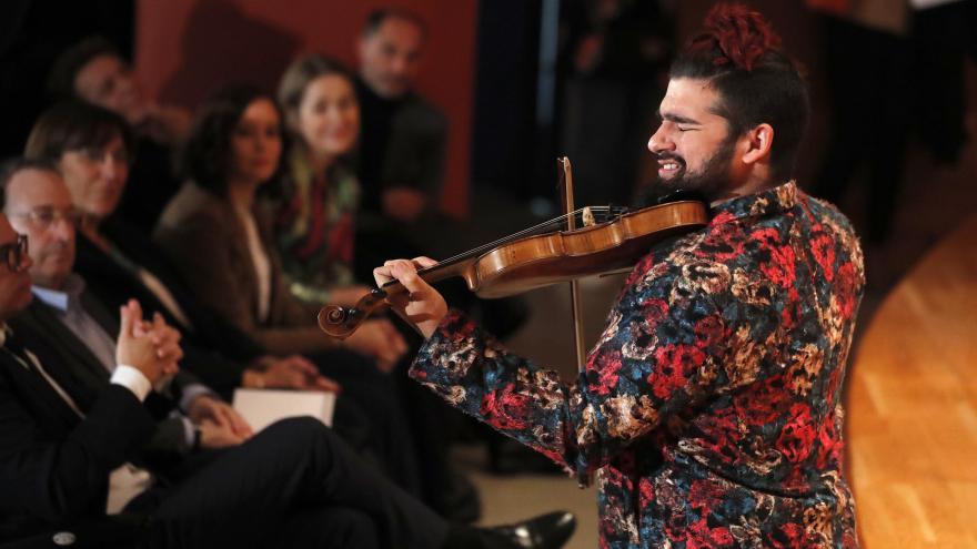 Isabel Díaz Ayuso durante la actuación de un violinista