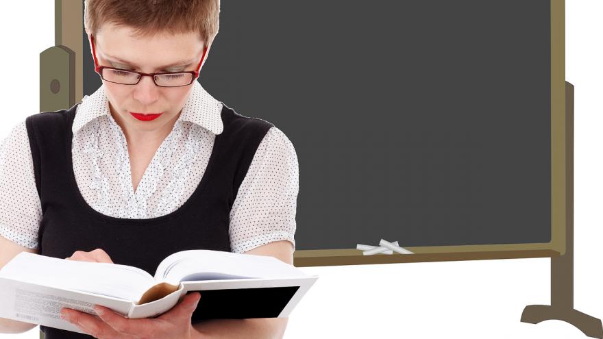 Profesora lee un libro con un fondo de pizarra de tiza