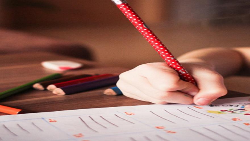 Niño escribiendo en una ficha escolar