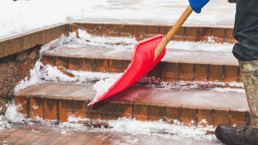 Hombre botas de goma quita nieve pala