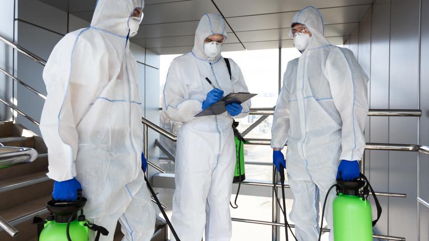 Hombres con traje de protección desinfección coronavirus