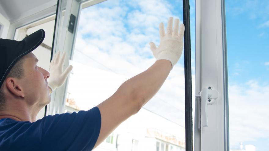 Persona conlocando cristal en una ventana