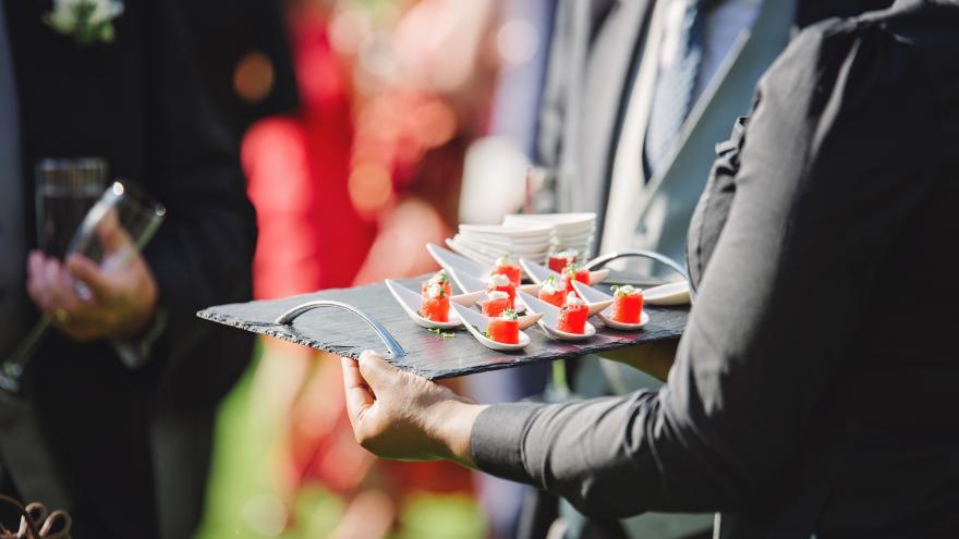 Camarero sirviendo canapés en evento al aire libre