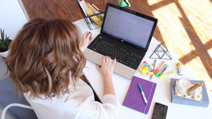 Mujer escribiendo en un ordenador sentada en una mesa con cosas de papeleria