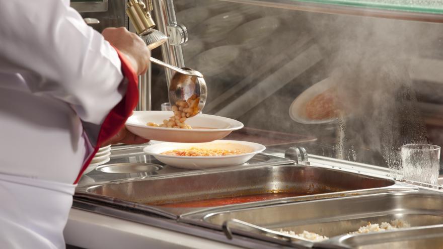 Una cocinera sirve en un comedor