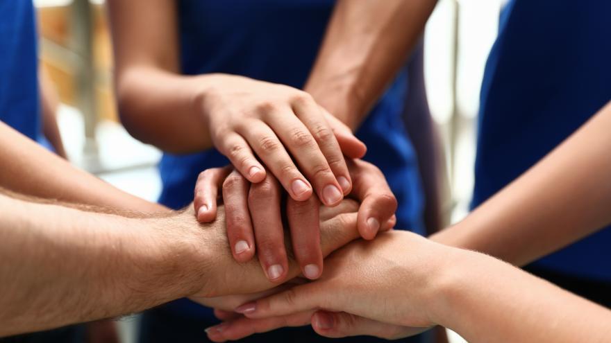 Voluntarios uniendo sus manos