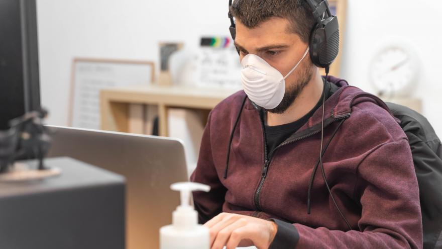 Una persona con mascarilla frente al ordenador