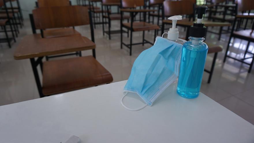 Una clase con una mascarilla y un bote de gel desinfectante