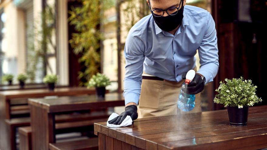 Un camarero con mascarilla desinfecta la mesa de la terraza