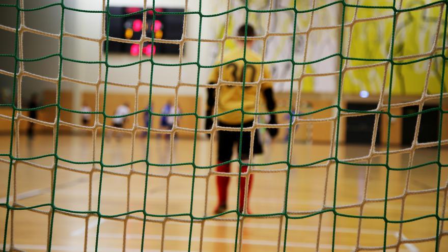Un portero de fútbol sala de espaldas visto a través de las redes de la portería