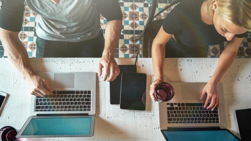 Un hombre y una mujer cada uno frente a su ordenador trabajando