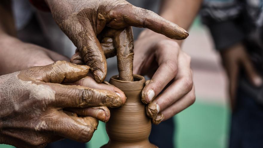 Dos personas trabajando una figura de cerámica en el torno