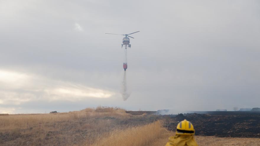 Un bombero de la Comunidad de Madrid y un helicoptero volando en el cielo mientras suelta agua