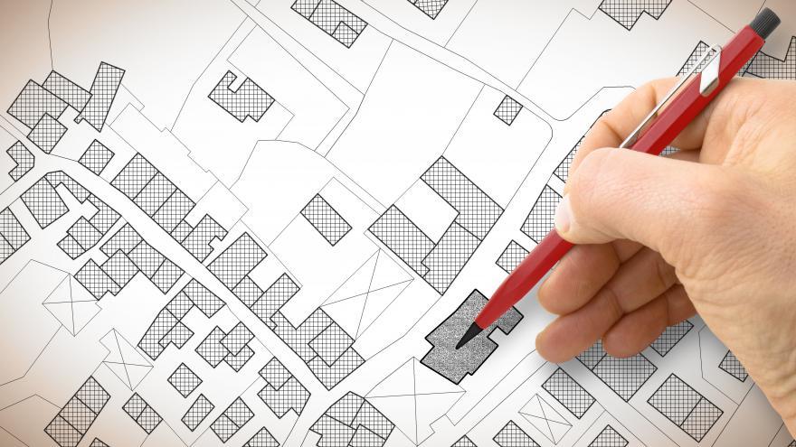 Mano con un lápiz dibujando un plano urbano
