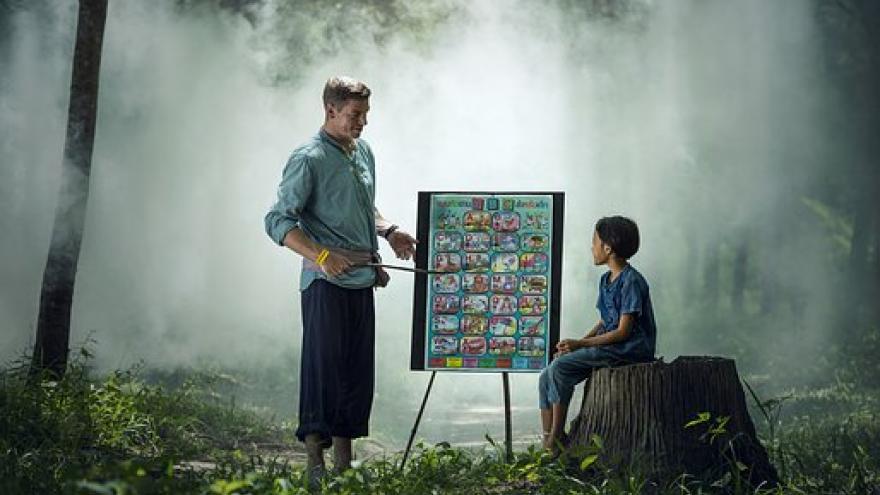 profesor y niño con pizarra