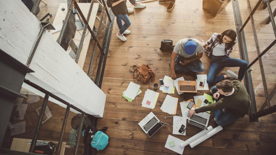 Jóvenes en el suelo trabajando en grupo