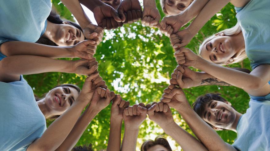 Manos de jóvenes unidas en círculo