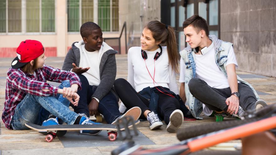 Adolescentes sentados en el suelo charlando
