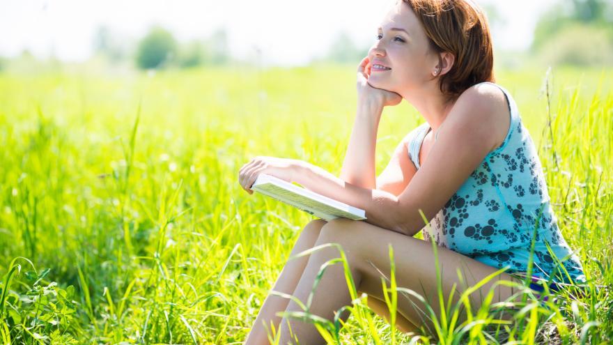 chica feliz leyendo sentada en la hierba