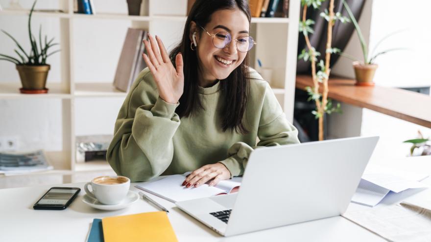 Mujer joven delante de ordenador saludando