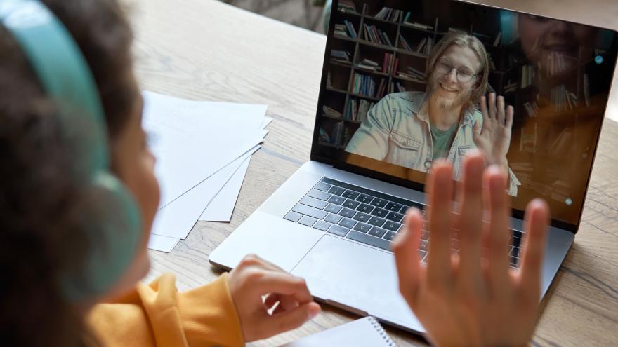 Mujer saludando a otra persona en el portátil
