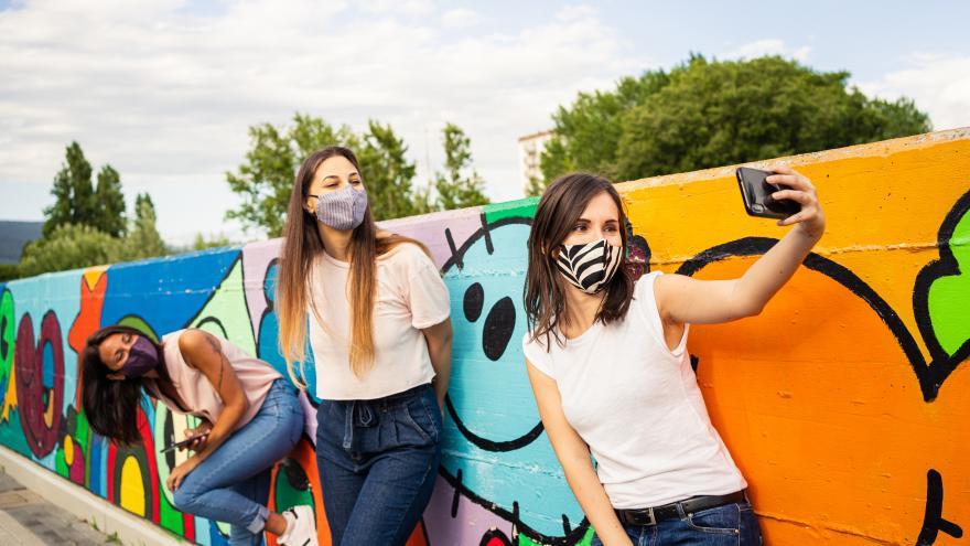 Chicas con mascarilla haciendo selfies