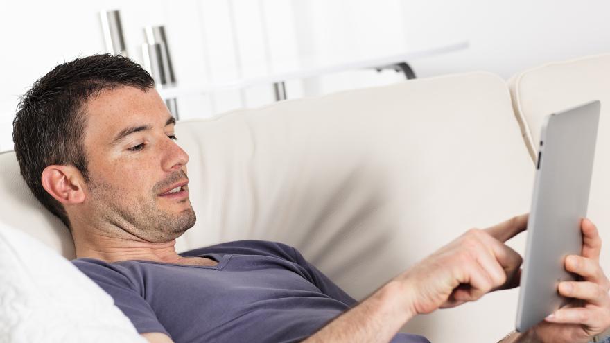 Señor con tablet en sofá