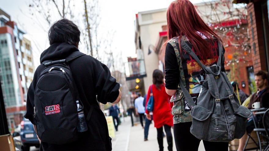 Dos jóvenes con mochilas a pie en la ciudad