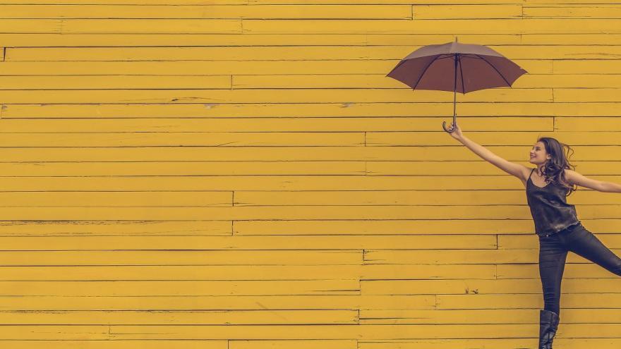 Joven con paraguas saltando sobre fondo amarillo