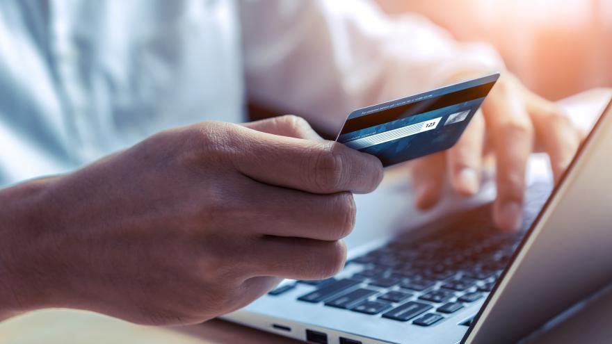 Un hombre sostiene una tarjeta de crédito frente al ordenador