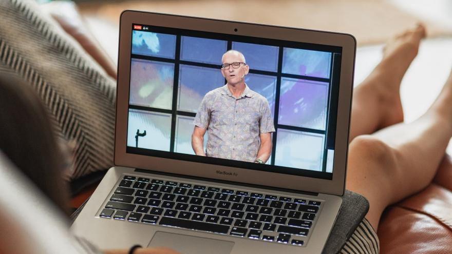 Joven con ordenador portátil sobre sus piernas viendo conferencia