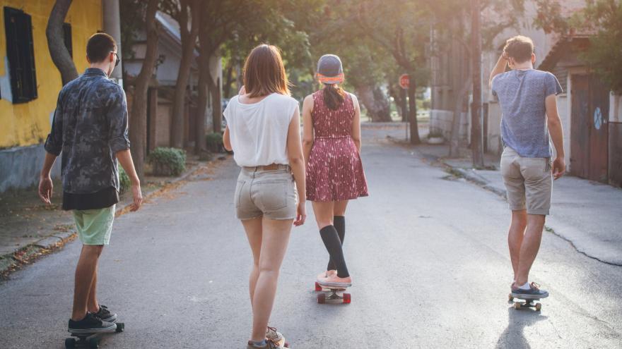 Jóvenes en patinete por una calle