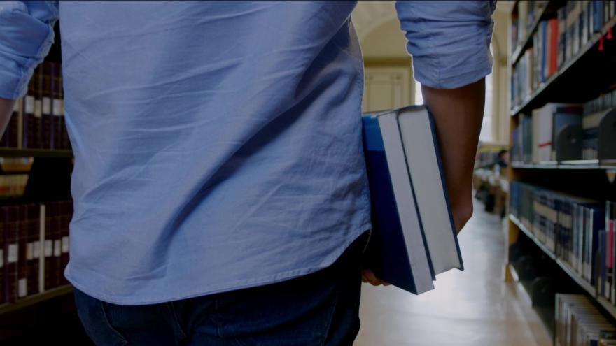 Joven de espaldas en un pasillo de biblioteca